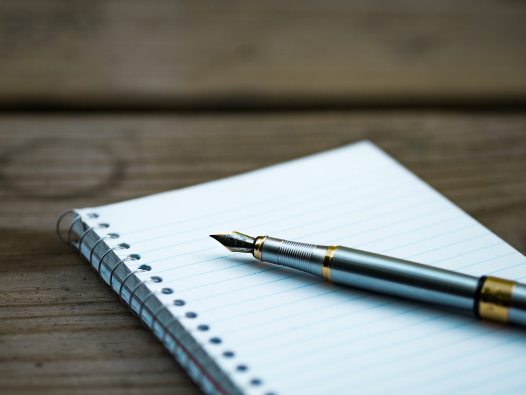 Blank notebook with a pen resting on it