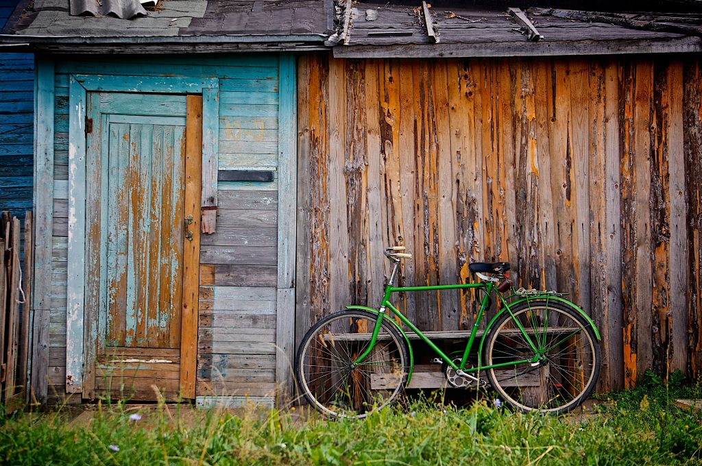 A bicycle resting against an old shed.