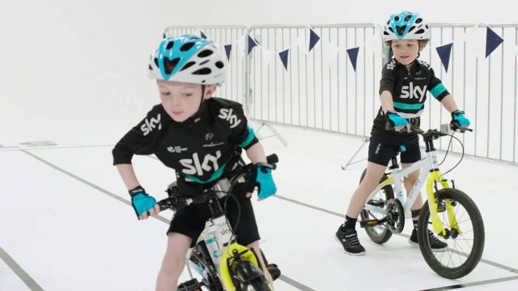 Still of Mini Team Sky. Two small boys on bikes wearing Team Sky kit.