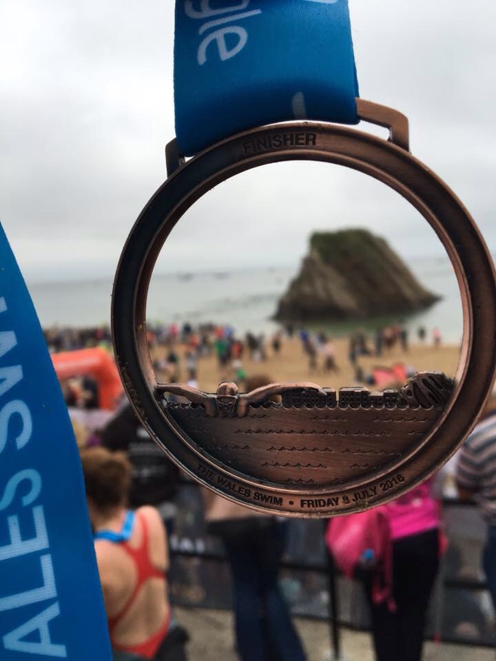 Looking through the LCW swim medal at Goscar Rock (a rock in the sea).