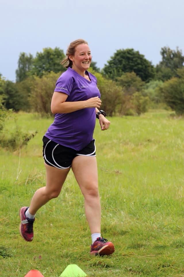 Tamsyn running. She is wearing a purple parkrun V25 t-shirt.