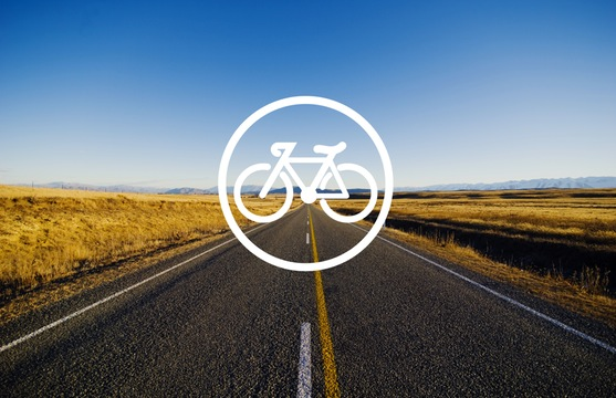A long straight open road with a icon of a bike superimposed on it.