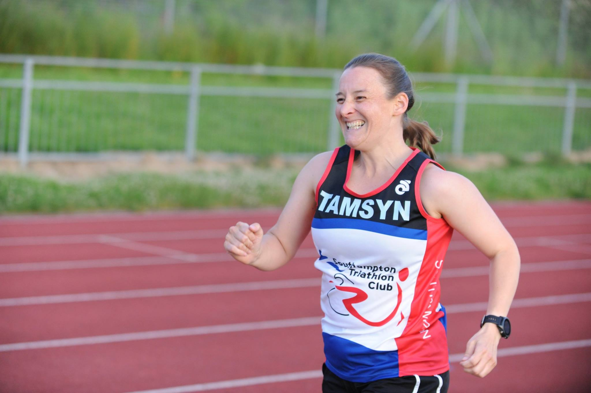 Tamsyn sprinting. She is smiling.