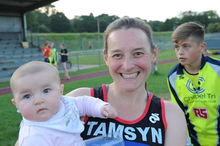 Tamsyn holding baby M. She is wearing running kit and is smiling at the camera.