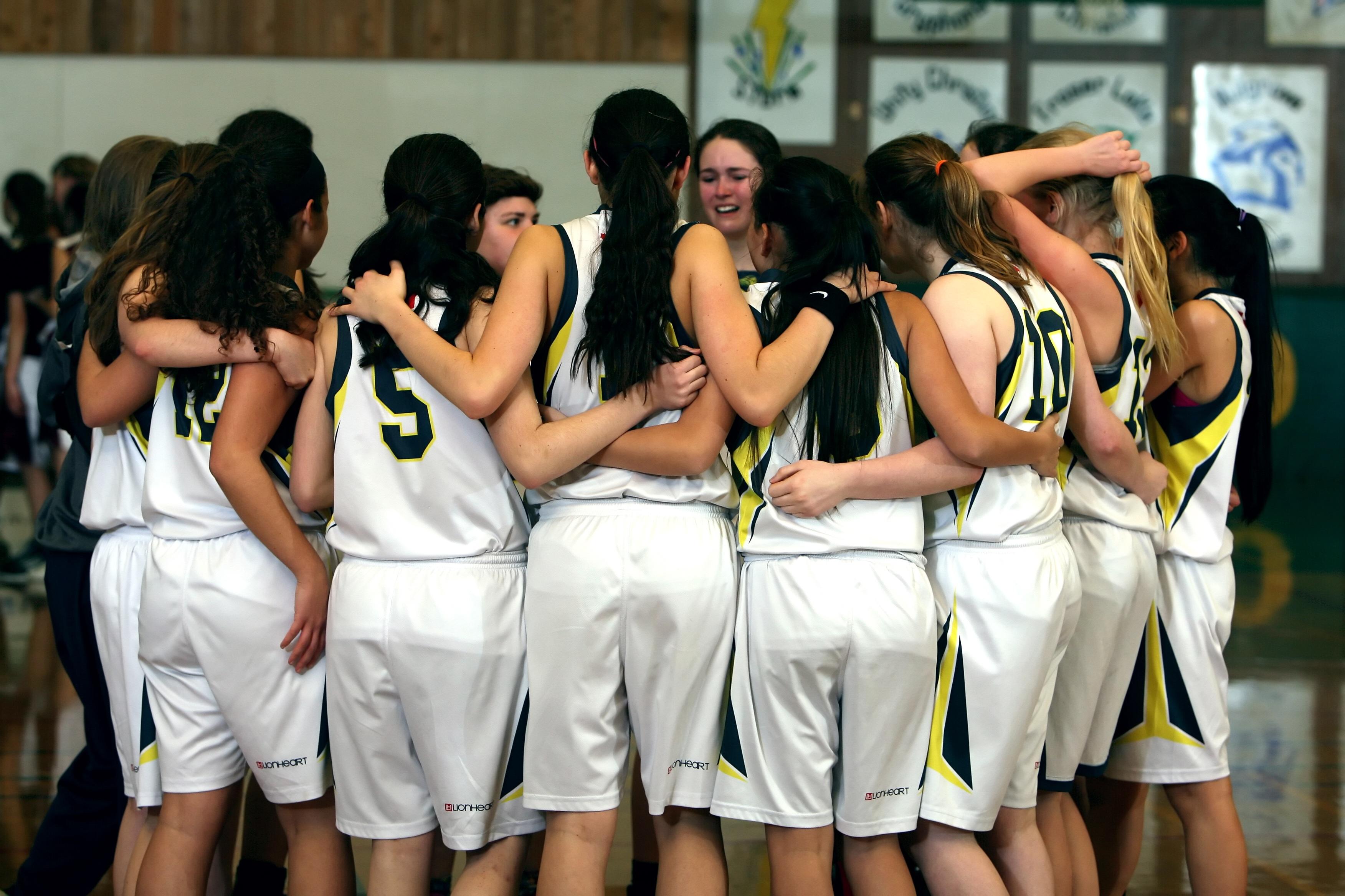 Girls basketball team huddled together.