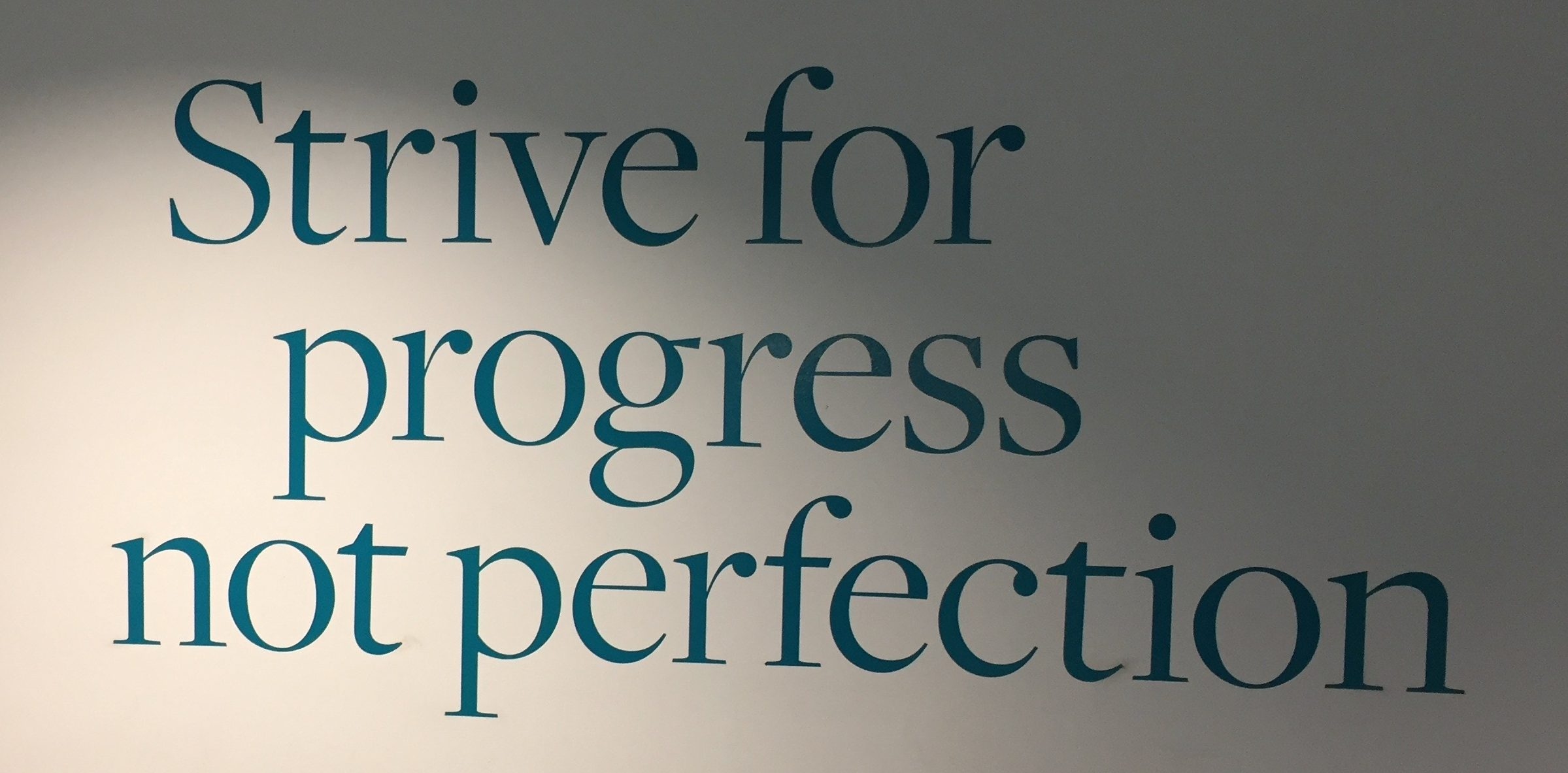 Wall sticker that says 'Strive for progress, not perfection'.