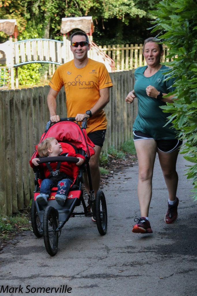 Tamsyn running alongside Stuart with M in her buggy.