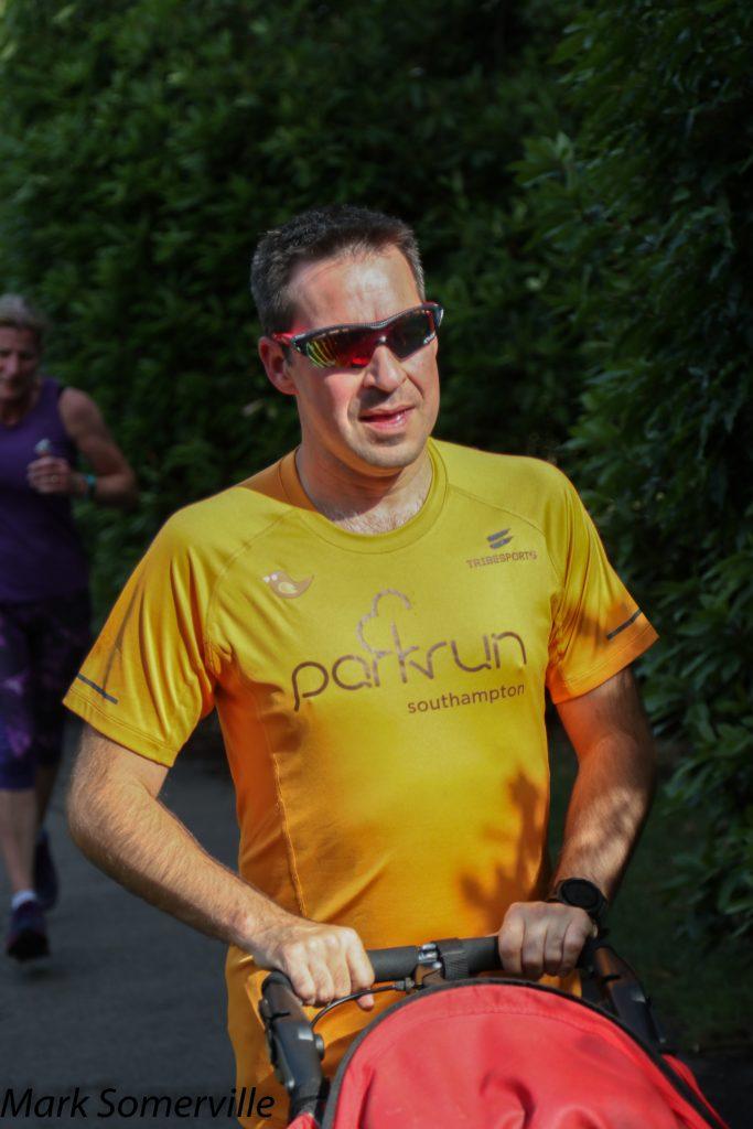 Stuart running. He is wearing a parkrun apricot t-shirt.