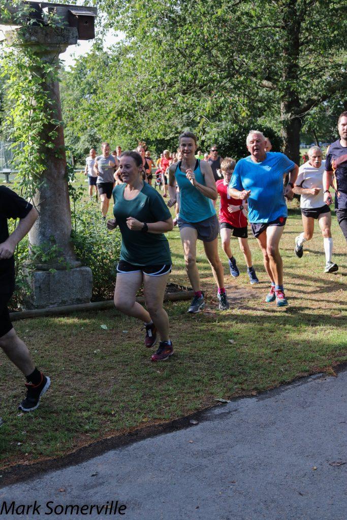 Tamsyn running at Lymington Woodside parkrun. She s wearing a green parkrun 250 t-shirt.