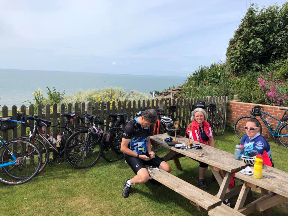 Three people sitting at a table in a garden by the sea. Bikes can be seen lined up along the fences.