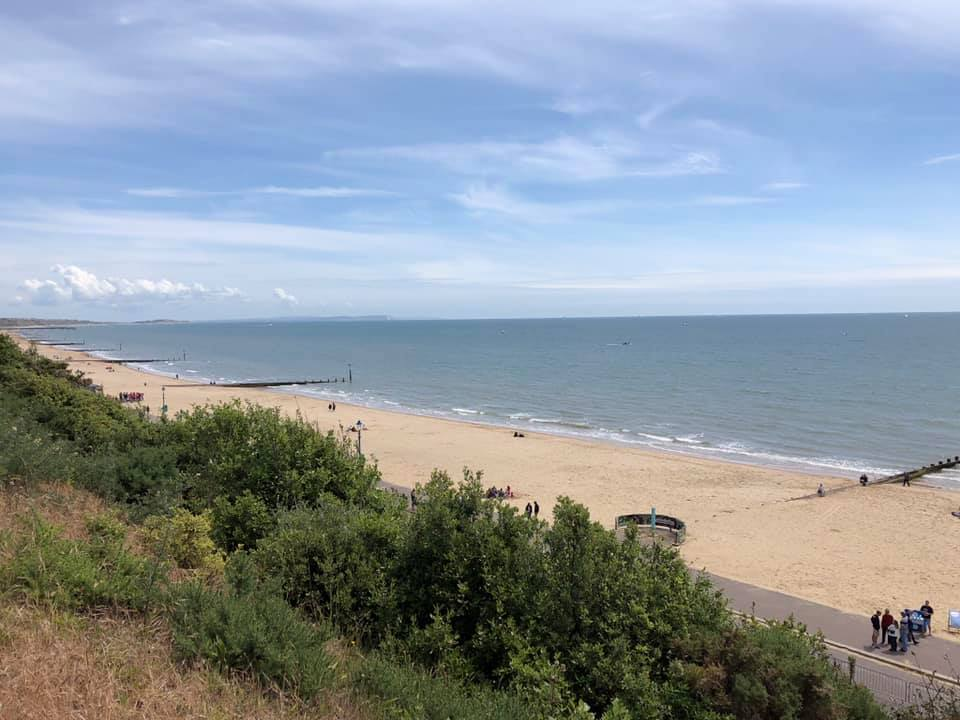 Bournemouth beach and sea. The sky is blue and dotted with light clouds.