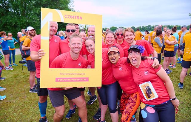parkrun ambassadors wearing raspberry t-shirts by a selfie frame.