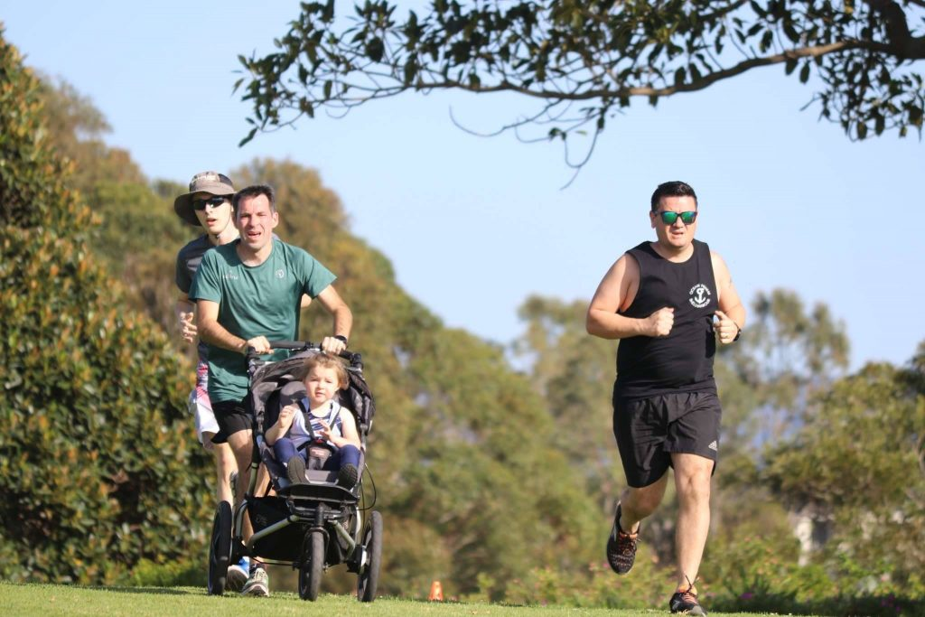 Stuart running to the finish with M in her buggy.