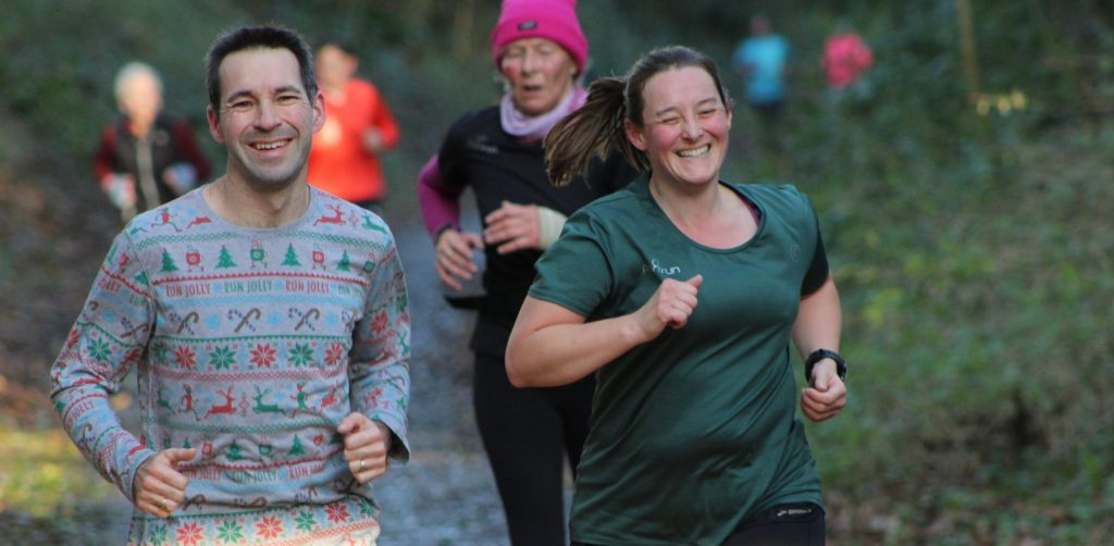 Tamsyn and Stuart running at Blandford parkrun. They're both smiling.