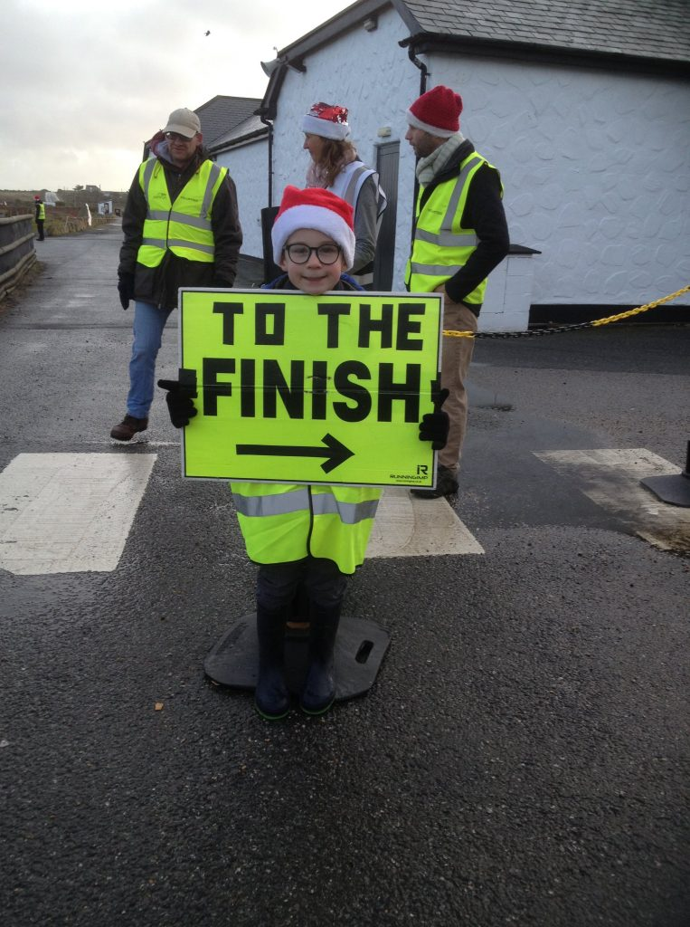 """Young marshall wearing a Santa hat and holding a sign saying """"To the finish""""."""