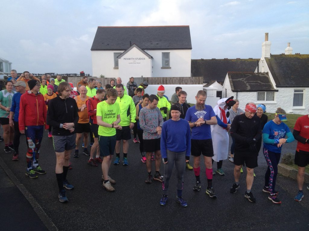 Runners all looking at their watches at the start of Land's End parkrun.