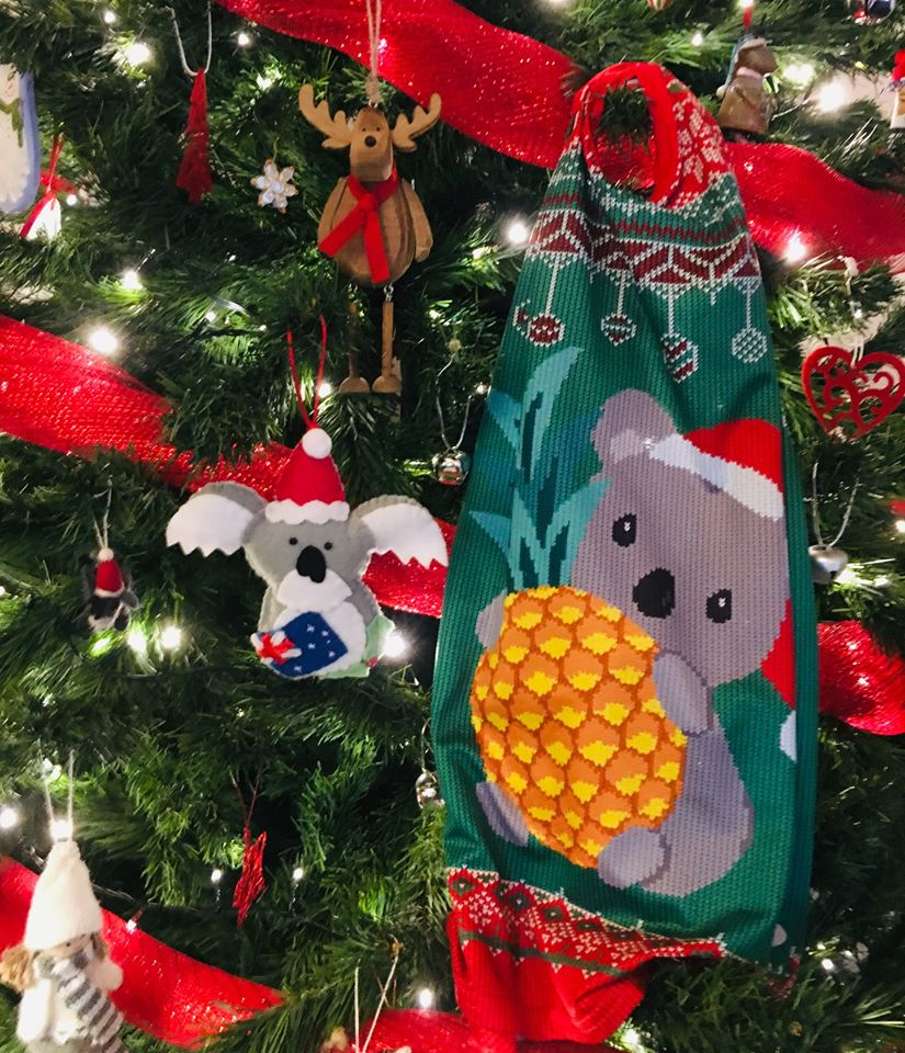 A running singlet featuring a koala holding a pineapple hanging on a Christmas tree.