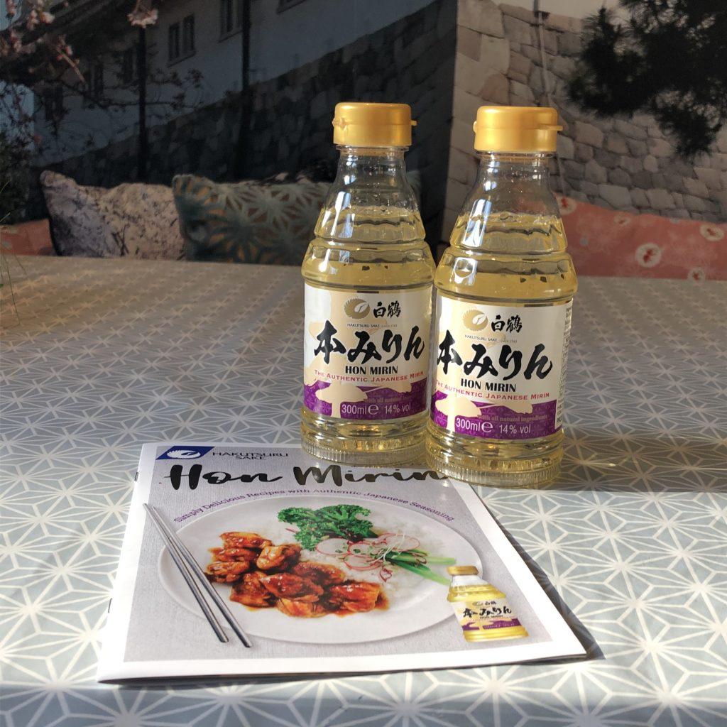 Two bottles of hon mirin by a leaflet with teriyaki chicken on it.