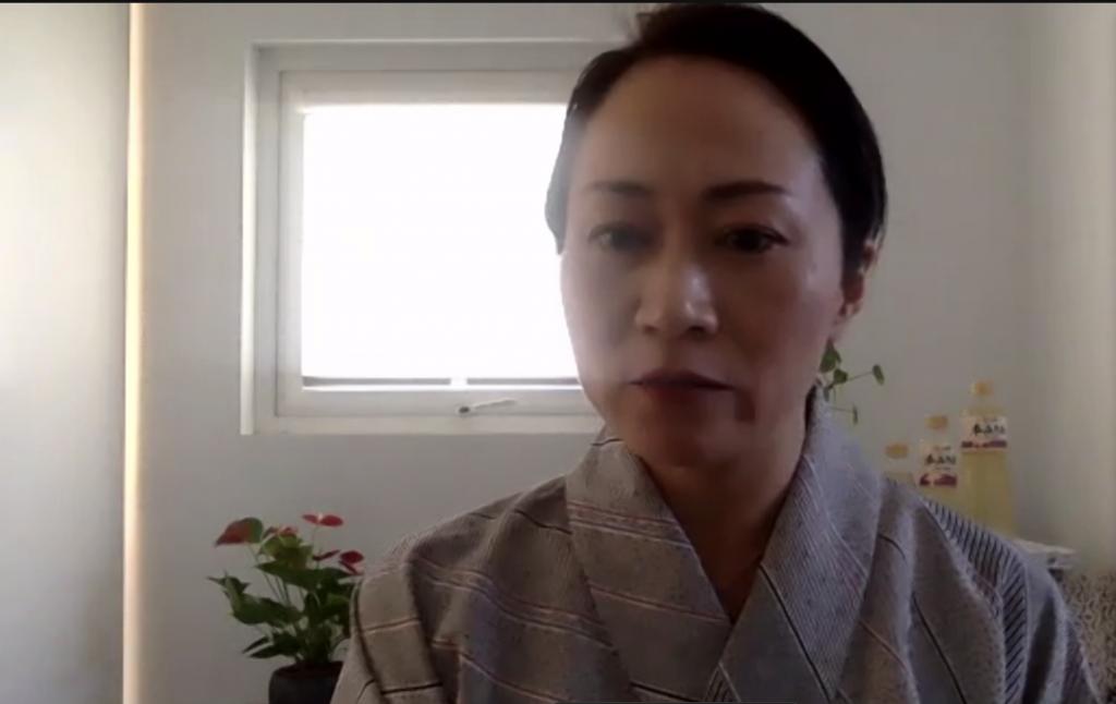 Izumi Nakamura wearing traditional Japanese clothes. Over her shoulder we can see three bottles if Hakutsuru mirin.
