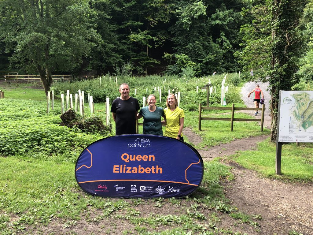 Pete (wearing a parkrun 100 top), Tamsyn (wearing a parkrun 250 t-shirt) and Ellie (in running clothes). They are standing behind a pop up parkrun sign that says Queen Elizabeth.