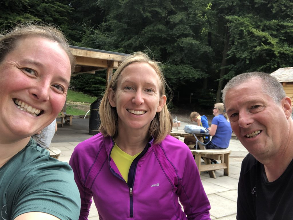 Tamsyn, Ellie and Pete dressed in running clothes. They are sitting at a picnic table outdoors.