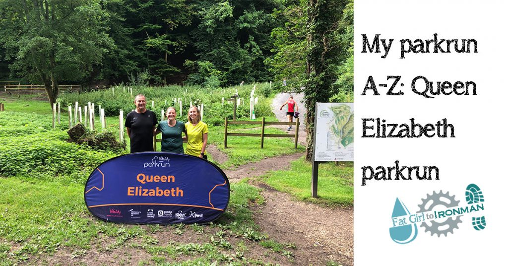 Tamsyn, Pete and Ellie behind a Queen Elizabeth parkrun sign.