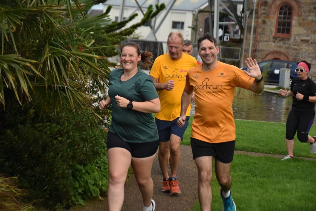 Tamsyn and Stuart running at Heartlands parkrun. Tamsyn is wearing a green 250 t-shirt and Stu has on a parkrun apricot t0shirt.
