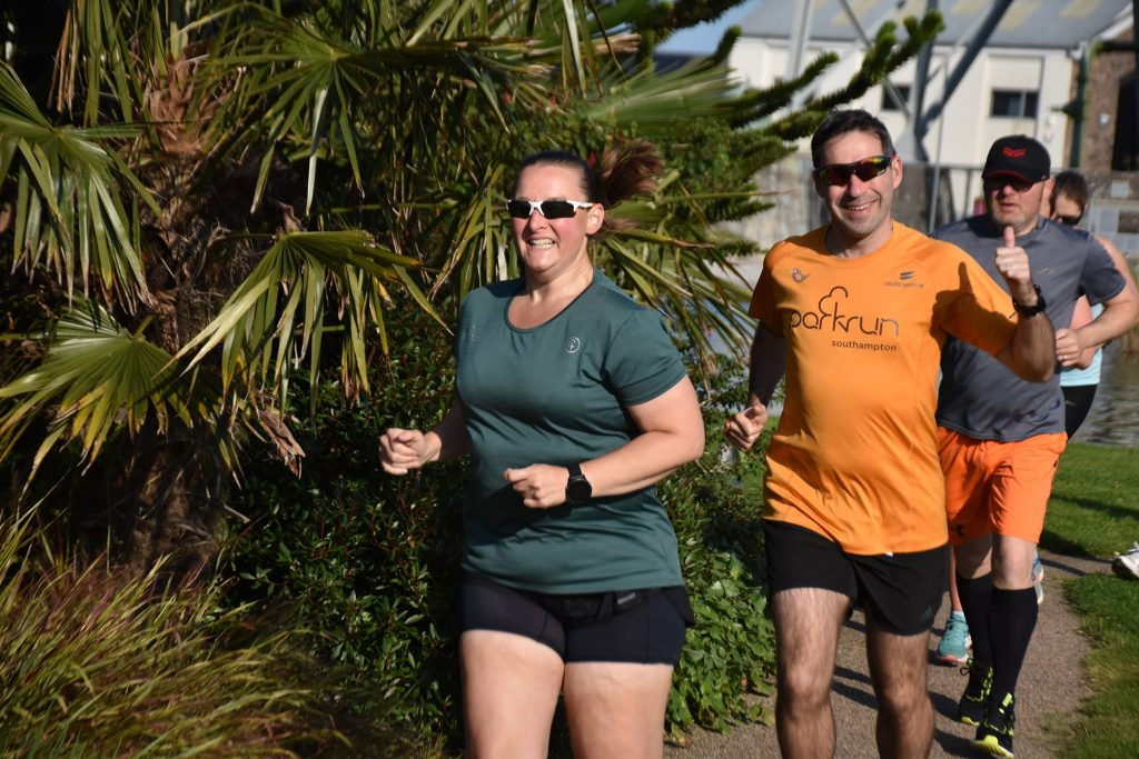 Tamsyn running at Heartlands parkrun. She is wearing a green 250 t-shirt. Stu is just behind her. He is giving a thumbs up.