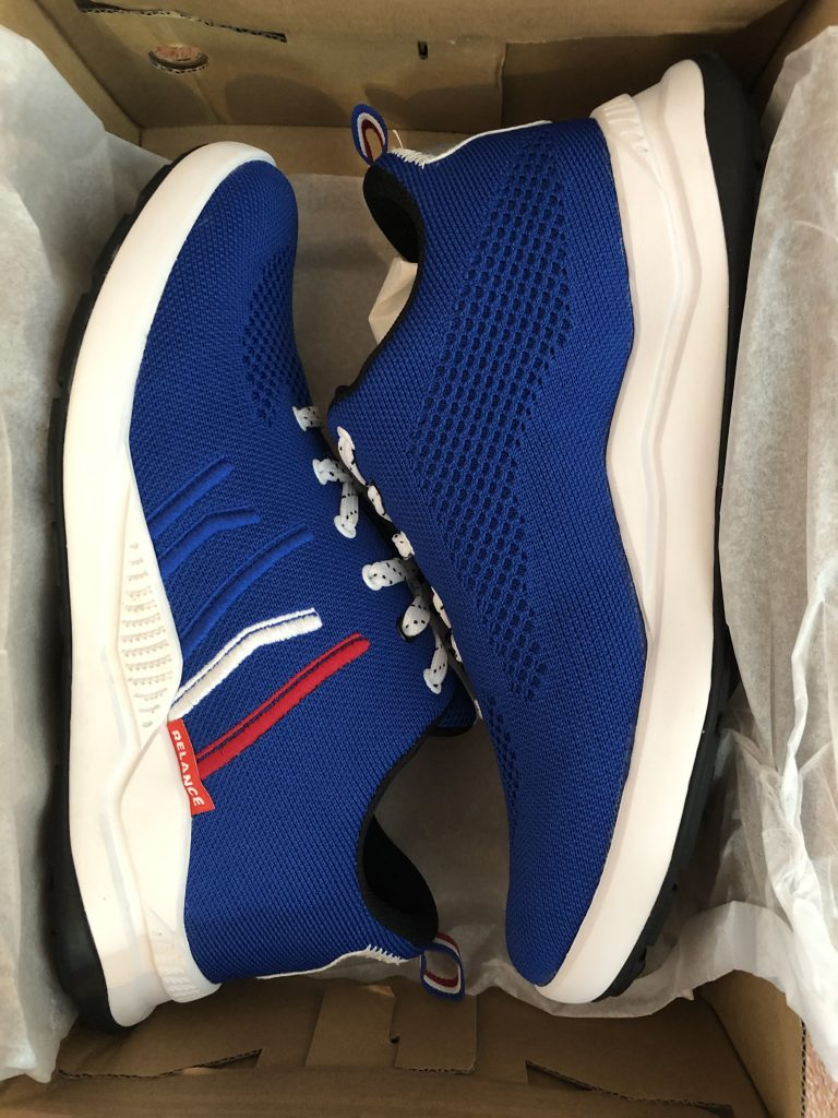 Two bright blue trainers nestled in a shoebox. They have red, white and blue decorative stitching.