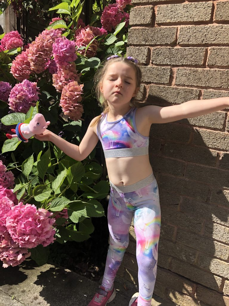 A small girl wearing leggings with unicorns and rainbows on them. She is posing with her eyes closed and holding a Peppa Pig toy.