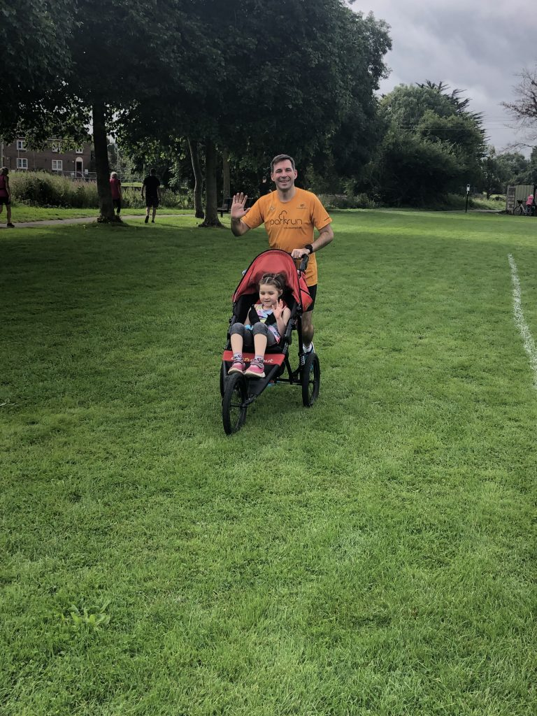 Stu pushing M in a buggy on grass. They are both waving.