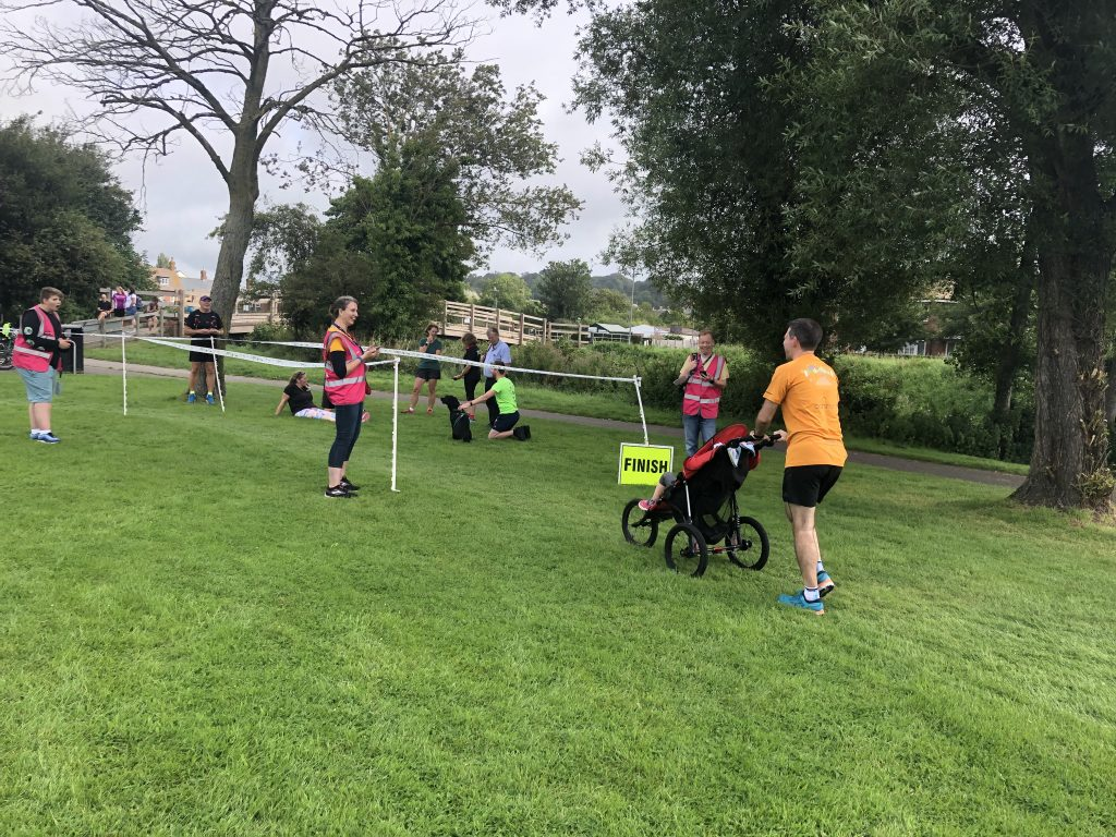 Stuart pushing a buggy across the finish line at St Mary's parkrun.
