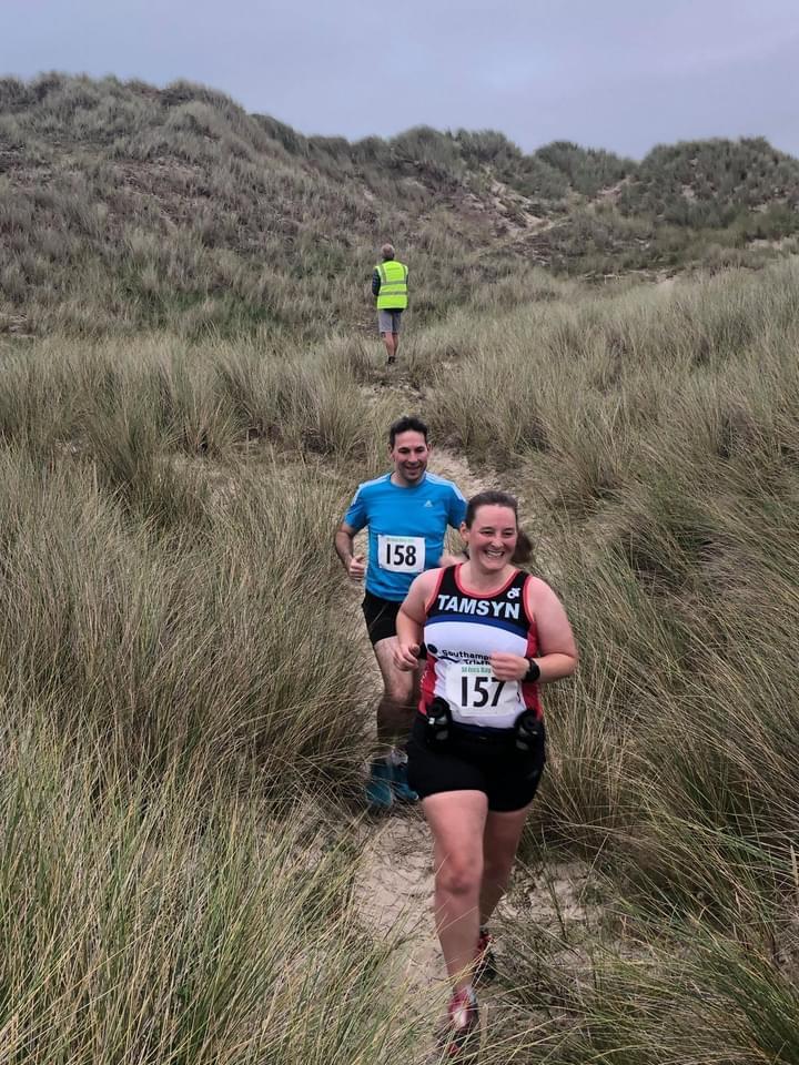 Tamsyn and Stuart running down a sand dune through marram grass.