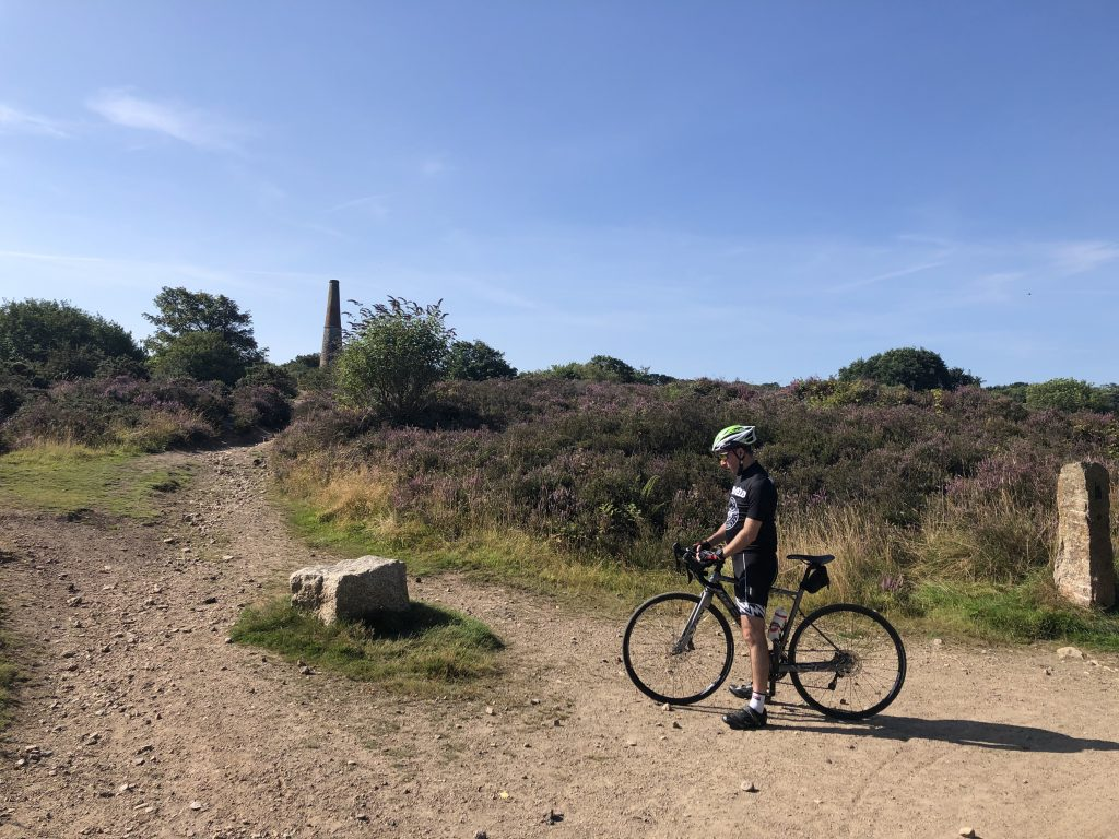 A dusty trail with heather next to it. A mine stack can be seen in the background. Stuart is astride his bike in the foreground.