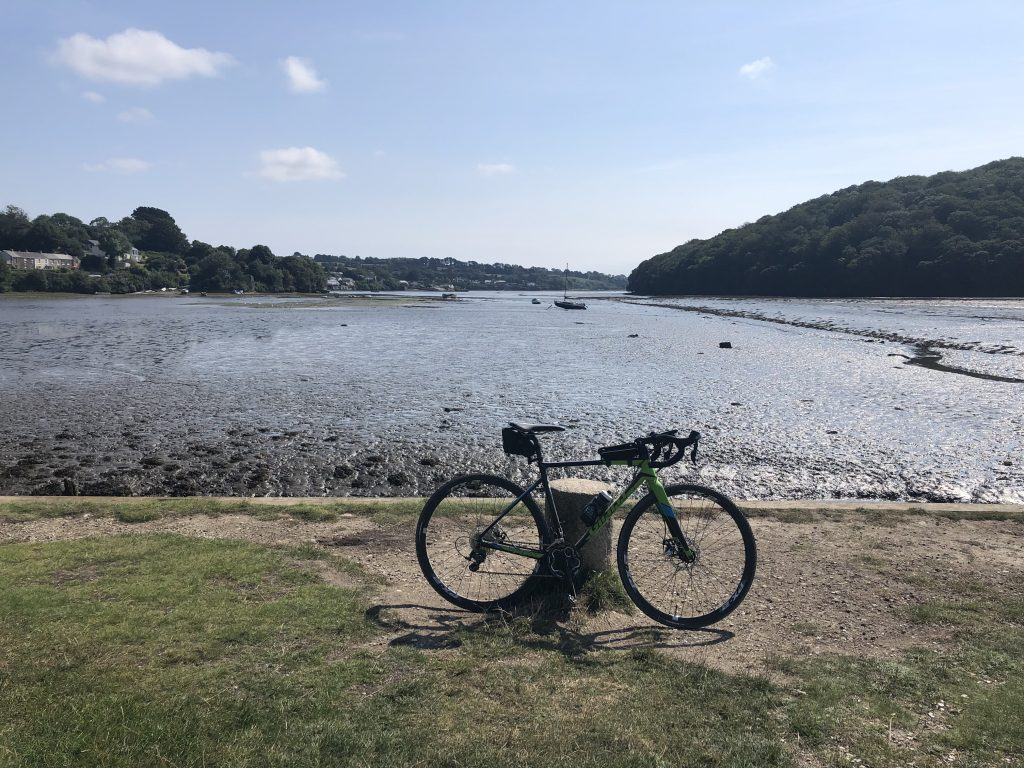 A bike resting against a post in front of Restronguet Creek. The tide is out.