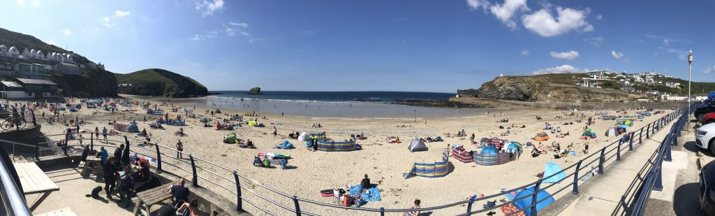 Panoramic view of the beach at Portreath. There is golden sand and many people have windbreaks up.