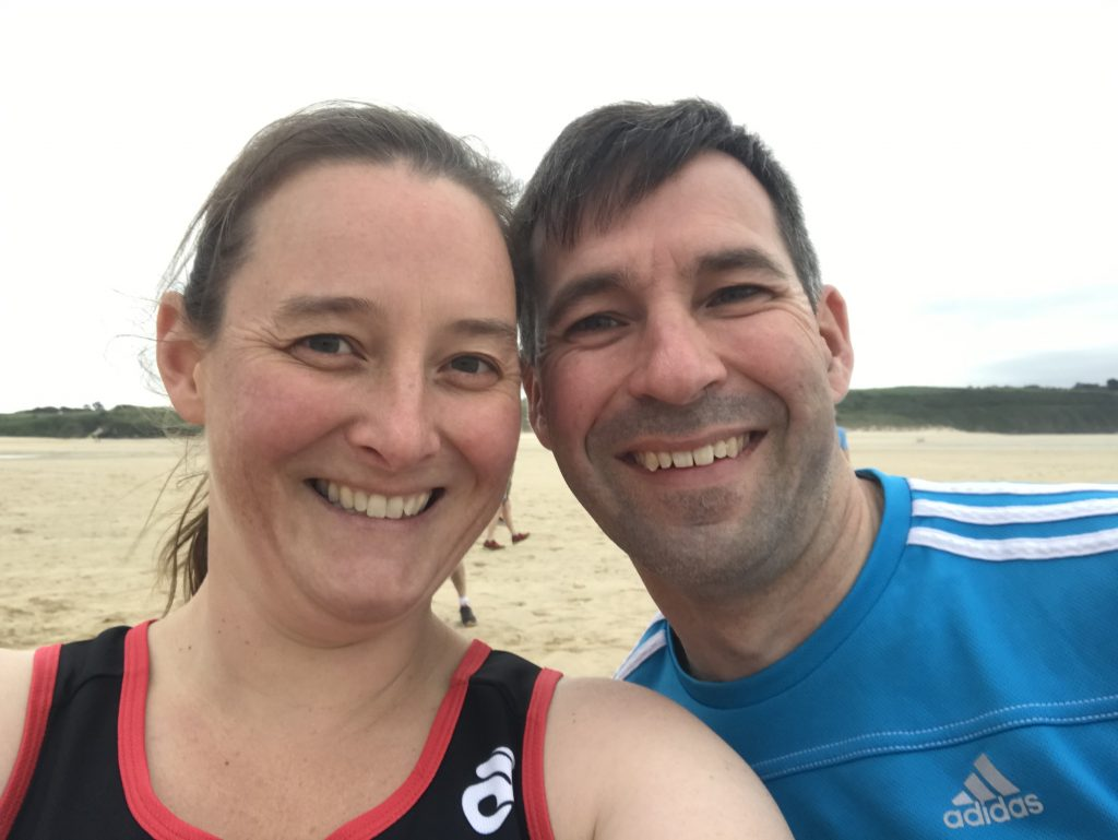 Two people (Tamsyn and Stuart) in running kit on a beach.