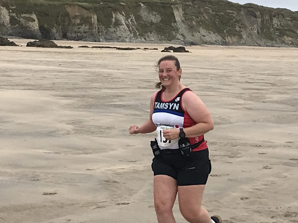 On the beach during St Ives Bay 10k. Tamsyn is smiling at the camera.