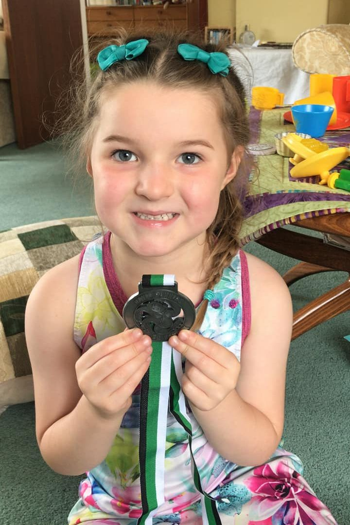 M holding a medal and smiling.